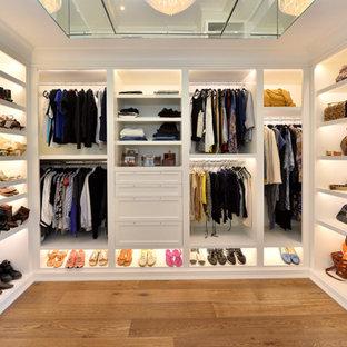 ニューヨークの広い男女兼用トランジショナルスタイルのおしゃれなウォークインクローゼット (オープンシェルフ、白いキャビネット、無垢フローリング、茶色い床) の写真