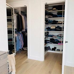 Esempio di una cabina armadio minimalista di medie dimensioni con ante lisce, ante bianche, parquet chiaro e pavimento multicolore