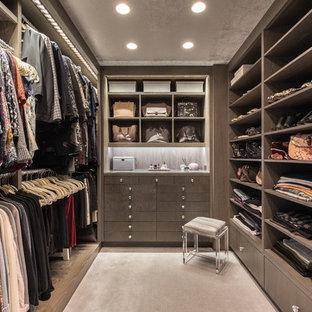 Modern inredning av ett walk-in-closet för kvinnor, med släta luckor, grå skåp, heltäckningsmatta och grått golv