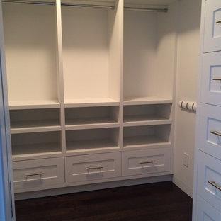 Modelo de armario vestidor unisex, clásico, de tamaño medio, con armarios con paneles empotrados, puertas de armario blancas y suelo de madera oscura