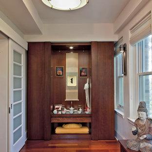 Aménagement d'un placard dressing asiatique avec un placard à porte plane, des portes de placard en bois sombre et un sol en bois brun.