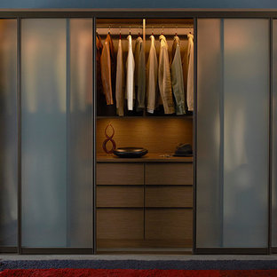 Mid-sized midcentury gender-neutral built-in wardrobe in Nashville with flat-panel cabinets, dark wood cabinets and concrete floors.