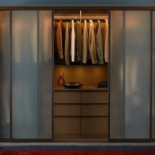 Cette photo montre un placard dressing rétro de taille moyenne et neutre avec un placard à porte plane, des portes de placard en bois sombre et béton au sol.