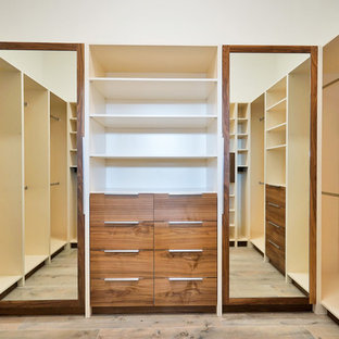 Large minimalist men's laminate floor and brown floor walk-in closet photo in Miami with flat-panel cabinets and dark wood cabinets