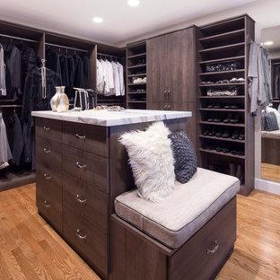 Modern inredning av ett stort walk-in-closet för könsneutrala, med släta luckor, mellanmörkt trägolv och bruna skåp