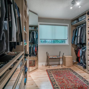This is an example of a mid-sized midcentury gender-neutral walk-in wardrobe in Calgary with light wood cabinets and light hardwood floors.