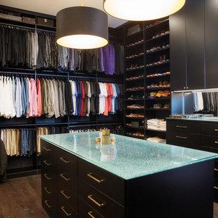 Foto de armario vestidor unisex, actual, con armarios con paneles lisos, puertas de armario negras, suelo de madera oscura y suelo marrón