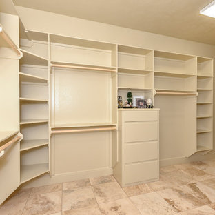 Photo of a large rustic gender neutral walk-in wardrobe in Other with beige cabinets, travertine flooring, flat-panel cabinets and beige floors.