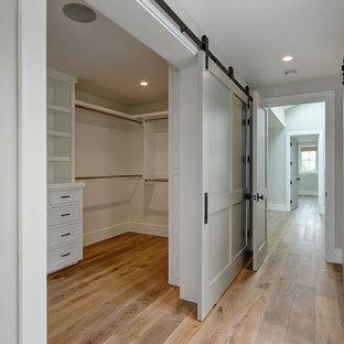 Diseño de armario vestidor tradicional, de tamaño medio, con puertas de armario blancas, suelo de madera en tonos medios y suelo marrón