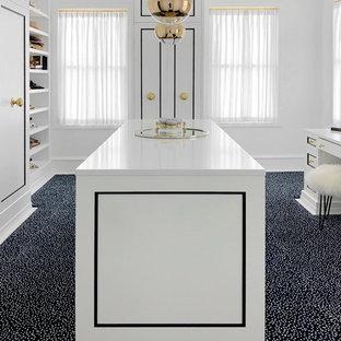 ニューヨークの巨大な女性用トランジショナルスタイルのおしゃれなウォークインクローゼット (落し込みパネル扉のキャビネット、白いキャビネット、カーペット敷き、白い床) の写真