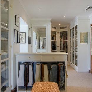 Ejemplo de vestidor unisex, rústico, grande, con armarios tipo vitrina, puertas de armario blancas y moqueta