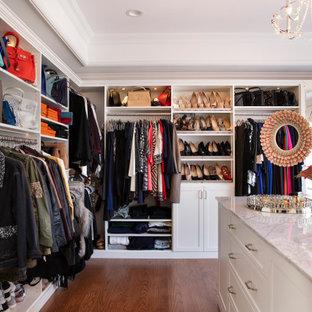 Imagen de armario y vestidor de mujer, marinero, grande, con armarios con paneles empotrados, puertas de armario blancas, suelo de madera en tonos medios y suelo marrón