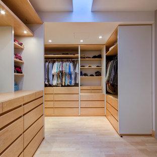 Esempio di una cabina armadio minimal con nessun'anta, ante in legno chiaro e parquet chiaro