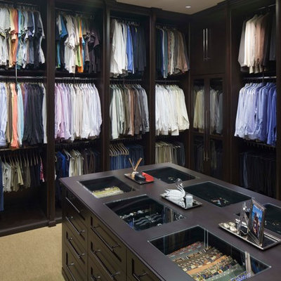 Elegant gender-neutral dressing room photo in Tampa with open cabinets and dark wood cabinets