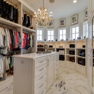This is an example of a mediterranean dressing room for women in Austin with white cabinets and marble flooring.