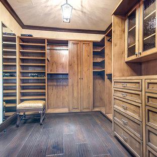 Imagen de vestidor unisex, mediterráneo, grande, con armarios con rebordes decorativos, puertas de armario de madera oscura y suelo de madera oscura