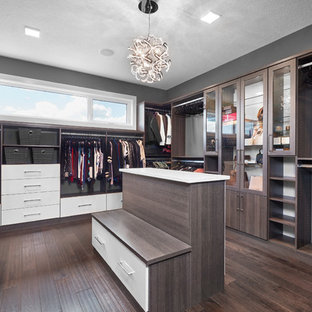 Design ideas for a large contemporary gender-neutral walk-in wardrobe in Edmonton with louvered cabinets, dark wood cabinets, dark hardwood floors and brown floor.