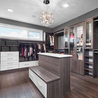 Foto på ett stort funkis walk-in-closet för könsneutrala, med luckor med lamellpanel, skåp i mörkt trä, mörkt trägolv och brunt golv