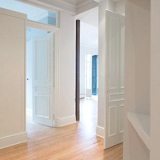 Imagen de vestidor unisex, bohemio, de tamaño medio, con puertas de armario blancas, suelo de madera en tonos medios, armarios con paneles lisos y suelo beige