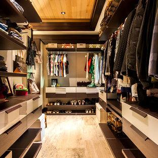 Idéer för att renovera ett mellanstort tropiskt walk-in-closet för könsneutrala, med släta luckor, skåp i mörkt trä, beiget golv och klinkergolv i porslin