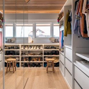 Esempio di una piccola cabina armadio unisex minimalista con ante di vetro, ante bianche, parquet chiaro, pavimento beige e soffitto a volta