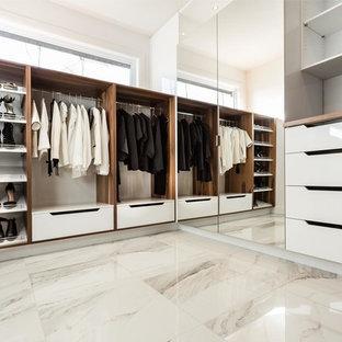 他の地域の広い男女兼用モダンスタイルのおしゃれなウォークインクローゼット (フラットパネル扉のキャビネット、中間色木目調キャビネット、大理石の床、白い床) の写真