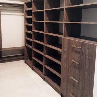 Modelo de armario vestidor unisex, minimalista, grande, con armarios con paneles lisos, puertas de armario de madera en tonos medios, suelo de baldosas de cerámica y suelo blanco