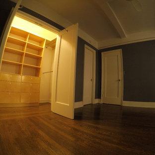 Foto de armario unisex, minimalista, de tamaño medio, con armarios con paneles empotrados, puertas de armario beige y suelo de madera clara