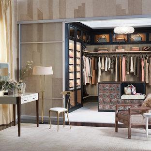 Modelo de armario vestidor de mujer, actual, grande, con armarios tipo vitrina, puertas de armario de madera en tonos medios y moqueta
