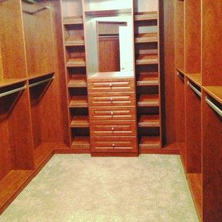 Imagen de armario vestidor unisex, tradicional, de tamaño medio, con armarios con paneles con relieve, puertas de armario de madera oscura y moqueta