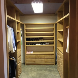 Large industrial gender-neutral walk-in wardrobe in Mexico City with open cabinets, medium wood cabinets, concrete floors and grey floor.