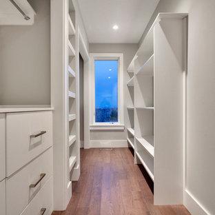 Modelo de armario vestidor unisex, minimalista, pequeño, con armarios con paneles lisos, suelo de madera en tonos medios y puertas de armario blancas