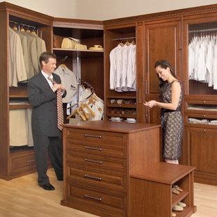Foto de armario vestidor de mujer, clásico renovado, grande, con armarios con paneles empotrados, puertas de armario de madera oscura y suelo de madera clara