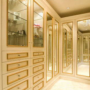 This is an example of a large traditional women's dressing room in San Francisco with beige cabinets, carpet and beige floor.