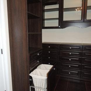 Modelo de armario vestidor unisex, tradicional, grande, con armarios con paneles con relieve, puertas de armario marrones y suelo de madera oscura