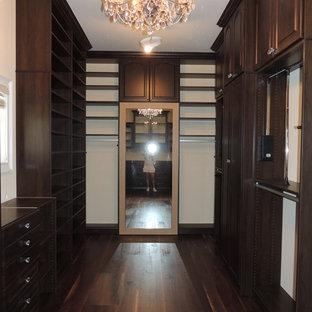 Inspiration pour un grand dressing traditionnel neutre avec un placard avec porte à panneau surélevé, des portes de placard marrons et un sol en bois foncé.