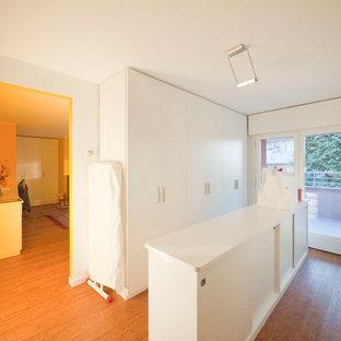 Ejemplo de armario unisex, moderno, grande, con armarios con paneles lisos, puertas de armario blancas y suelo de bambú