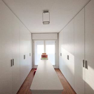 Imagen de armario vestidor unisex, moderno, grande, con armarios con paneles lisos, puertas de armario blancas y suelo de bambú