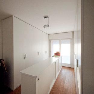 Imagen de armario unisex, moderno, grande, con armarios con paneles lisos, puertas de armario blancas y suelo de bambú