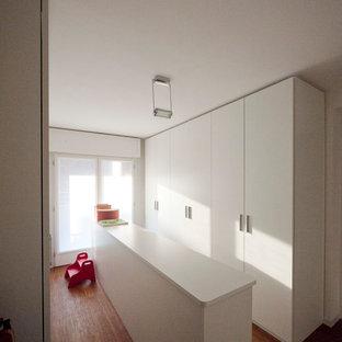 Cette image montre un grand placard dressing minimaliste neutre avec un placard à porte plane, des portes de placard blanches et un sol en bambou.