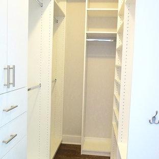 Modelo de armario vestidor industrial, extra grande, con armarios con paneles lisos, puertas de armario blancas y suelo de madera oscura