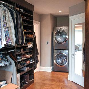 Diseño de armario vestidor de hombre, tradicional renovado, extra grande, con armarios con paneles lisos, puertas de armario marrones y suelo de madera en tonos medios