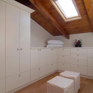 Modern inredning av ett walk-in-closet, med vita skåp och ljust trägolv