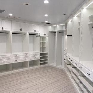 Foto de armario vestidor clásico, grande, con armarios con paneles con relieve, puertas de armario blancas y suelo beige