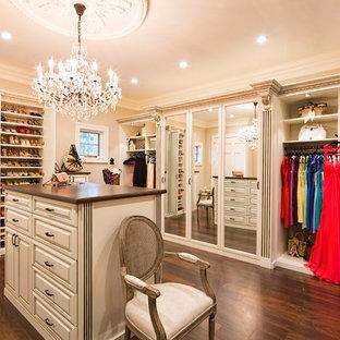 Modelo de armario vestidor de mujer, tradicional, grande, con puertas de armario blancas, suelo marrón, armarios con paneles con relieve y suelo de madera oscura
