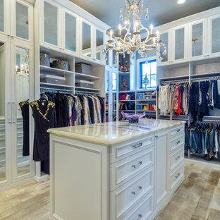 Foto på ett stort vintage walk-in-closet för könsneutrala, med vita skåp, ljust trägolv och luckor med infälld panel