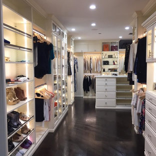 This is an example of a large midcentury women's walk-in wardrobe in Los Angeles with glass-front cabinets, dark hardwood floors, black floor and beige cabinets.