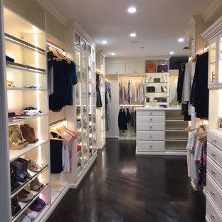 ロサンゼルスの広い女性用ミッドセンチュリースタイルのおしゃれなウォークインクローゼット (ガラス扉のキャビネット、濃色無垢フローリング、黒い床、ベージュのキャビネット) の写真