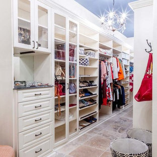 Example of a mid-sized transitional terra-cotta floor walk-in closet design in Los Angeles with white cabinets and raised-panel cabinets