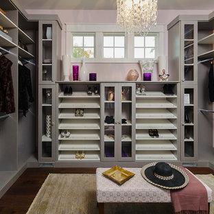 Diseño de armario vestidor de mujer, tradicional renovado, de tamaño medio, con armarios con paneles lisos, puertas de armario grises y suelo de madera oscura